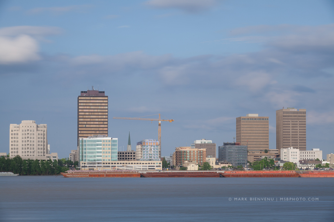 Barges on the Mississippi River in front of the Baton Rouge skyline | Louisiana Travel Photographer Mark Bienvenu